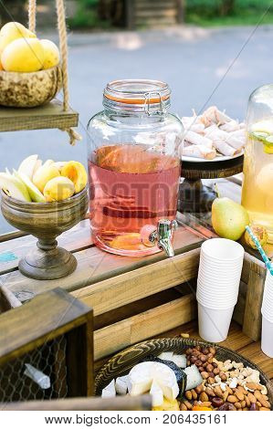 country lifestyle, drinks, rural products concept. generous amount of wonderful confection in wooden vases surrounding huge jar with bright pink homemade compot