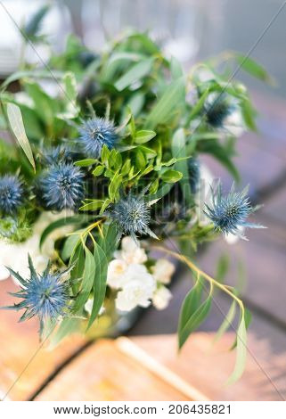 flower arrangement, gifts of nature, summer concept. simple but cute little bunch composed of wild flowers of eryngo, also named as amthyst sea holly, and leaves of eucalyptus