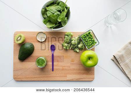 baby food, healthy eating and nutrition concept - glass jar with green vegetable puree, feeding spoon and fruits on wooden board