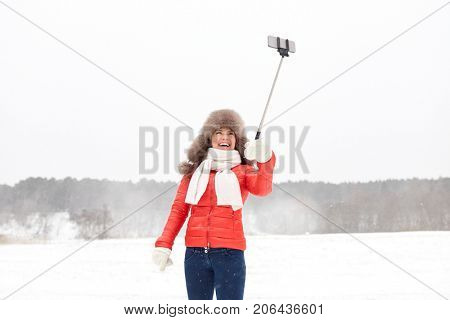 people, technology and leisure concept - happy woman in winter fur hat taking picture by smartphone on selfie stick outdoors