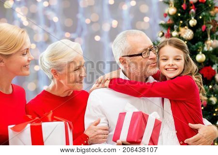 winter holidays, family and people concept - happy grandparents and granddaughter with christmas gifts over lights background