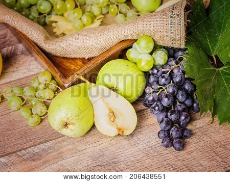 Juicy, green and purple, fresh grape and nutritious pears on a rustic fabric background. Different appetizing fruits for vegetarians.