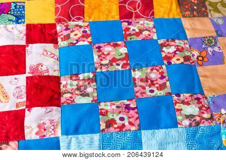 garment industry, needlework, homemade, quilting, interior, design concept - masterpiece of sewing made of colorful textile scraps in geometric forms with various ornaments