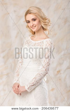 fashionable gown, beautiful blonde model, bride hairstyle and makeup concept - young smiling woman in white wedding festive dress standing indoors on light background, romantic slender girl posing
