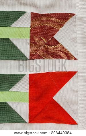 patchwork, sewing, fashion concept - macro on beautiful quilt sewn from scraps of colored cloths in feed of certain geometric shapes, close-up on different flaps of stitched material, flat lay