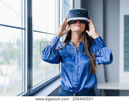 A pretty funny girl in 3D virtual reality glasses enjoys trip in an adventurous world in the office. Female action in virtual reality helmet. Digital VR device. A concept of global web.