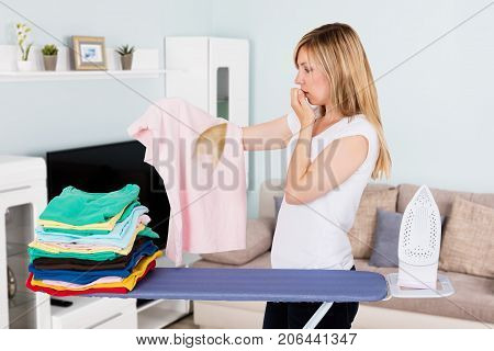 Worried Young Woman Looking At Pink T-shirt With An Iron Burn In Living Room