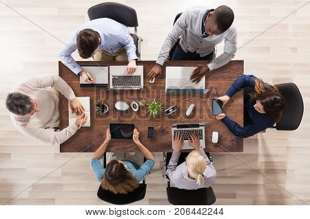 Elevated View Of Businesspeople Using Laptop And Digital Tablet In Office Over Wooden Desk