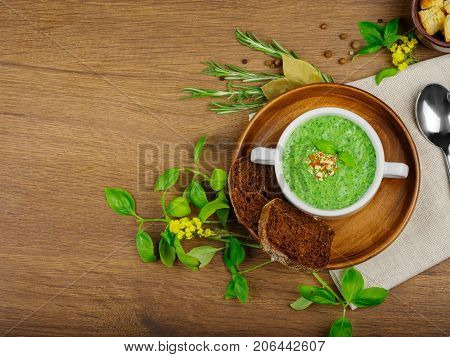 Green vegetable cream soup with celery and broccoli. Black bread with garlic and onions. Crackers of white bread. Many fresh and healthy vegetables. Close-up of cream soup. Copy space. Food concept.