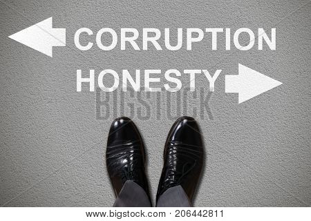 Low Section View Of Human Foot With Arrow Sign Showing Direction Towards Corruption And Honesty