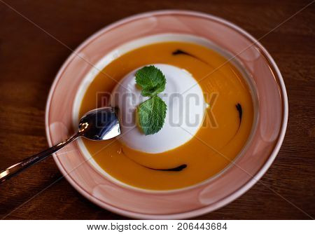 Dessert white panna cotta with mango juice on the plate
