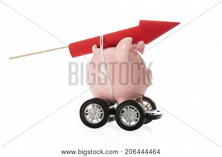 Red Rocket Firework Tied Up With Rope On Piggy Bank Over White Background