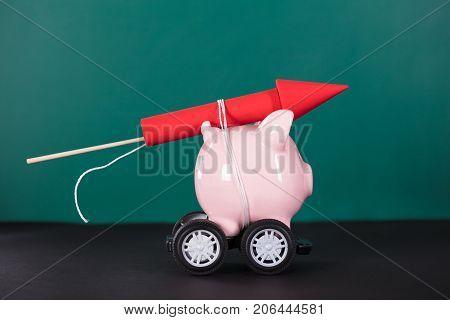 Red Rocket Firework Tied Up With Piggy Bank Over Black Background