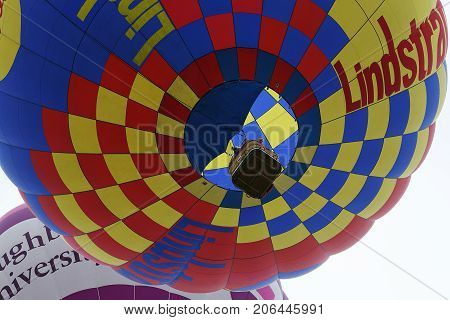 Bristol, UK: August, 2016: Two people peer over the basket as a hot air balloon rises at the Bristol International Balloon Fiesta. The annual event has become Europe's largest hot air balloon festival