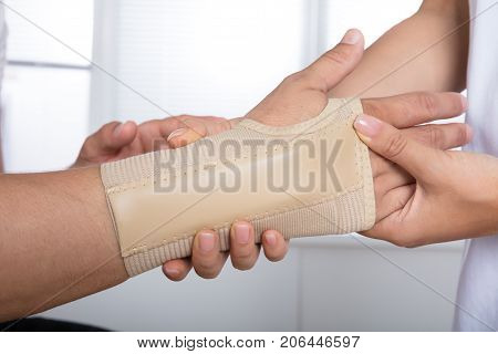 High Angle View Of A Orthopedist Fixing Plaster On Injured Person's Hand In Hospital