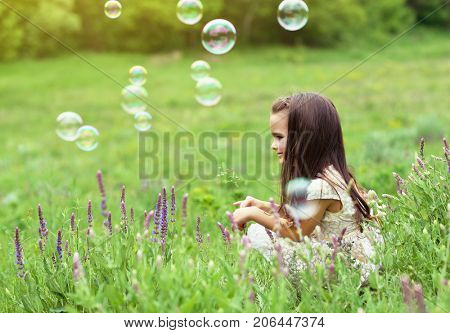 Cute little girl on a forest glade among lush vegetation and around fly soap bubbles. Kid with soap bubbles over nature outdoor.
