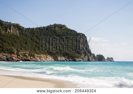 Beautiful Cleopatra beach in Alanya Turkey with turquoise water waves and castle rock of Alanya covered by pine forests