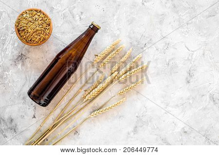 Ingredients for beer. Malting barley near beer glasses and bottle on grey background top view.
