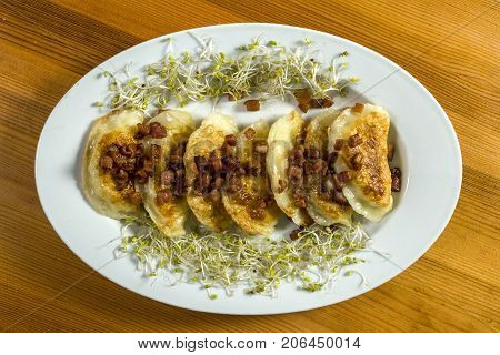 Fried dumplings with cheese and pork scratching on wooden table. Polish ukrainian russian traditional food.Fried dumplings with cheese and pork scratching on wooden table. Polish ukrainian russian traditional food.