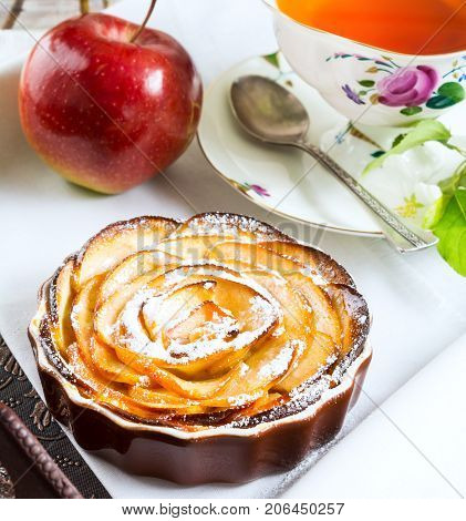 Apple rose shaped pie and cup of tea on the serving tray. Breakfast tea with sweet apple pastry.