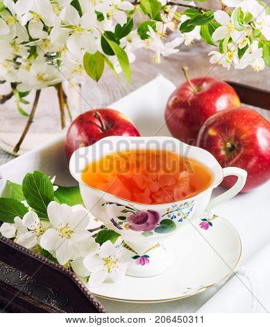 Cup of tea on wooden table and apple blossom on vintage serving tray. Tea time concept.