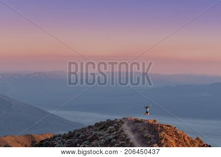 Woman Leaps At Sunset In Death Valley Mountains