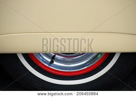 Vintage car skirts and classic whitewall tire displayed outdoors.