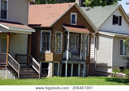 JOLIET, ILLINOIS / UNITED STATES - JULY 25, 2017: A small house with a broken porch on Broadway Street, in one of Joliet's less affluent neighborhoods.