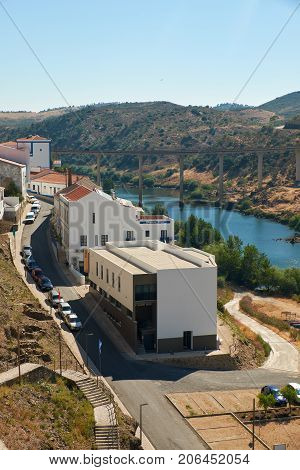 MERTOLA PORTUGAL - JUNE 30 2016: View of Rua Dr. Afonso Costa in small town of Mertola with the Bridge over the Guadiana river on the background. Portugal
