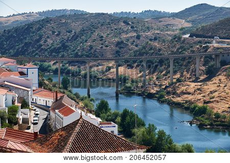 MERTOLA PORTUGAL - JUNE 30 2016: The view of bridge across the valley of Guadiana river with residential houses of Mertola on the foreground. Mertola. Portugal