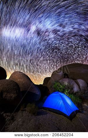 Star trails with the Milky Way show an astrologers heaven at a camping site in Joshua Tree California