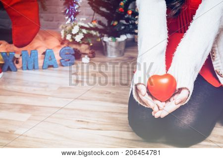 hand holding a red heart Happy young lady Christmas tree New year concept vintage tone