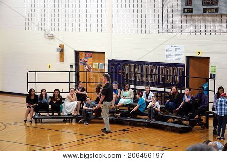 JOLIET, ILLINOIS / UNITED STATES - MARCH 23, 2016: Drauden Point Middle School students sit on risers, in the gymnasium, prior to performing in the school's annual talent show.