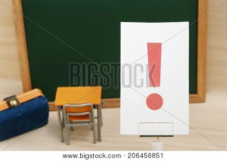 Exclamation mark on white paper with the study tool as the background. Concept of learning inspiration concept.
