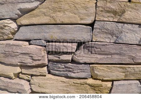 Stone wall made with flagstone, decorative rock, building stone and dimensional stone.