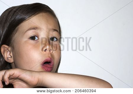 Cold. Child cough. A pre-school girl coughs covering herself with her hand. The spread of the virus