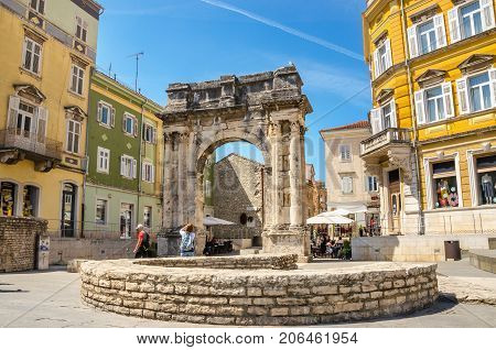 Ancient Roman triumphal arch or Golden Gate and sunny square in Pula, Croatia, Europe