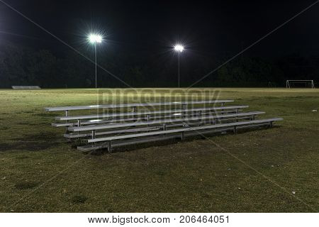 Metal bleachers on an empty soccer field at night with the lights on and water drops sparkling on the seats from a recent rain.