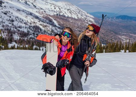 Two Young Women With Ski And Snowboard