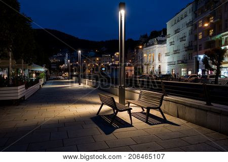 Czech Republic. Karlovy Vary. Embankment of the river Tepl in the evening of September 1, 2017. In the foreground there are street benches and a lantern. Night time.