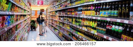 BANGKOK THAILAND - AUGUST 12: Unidentified shoppers shop in the soy sauce aisle in Foodland Supermarket as an unidentified store Keeper organizes inventories on August 12 2017 in Bangkok.