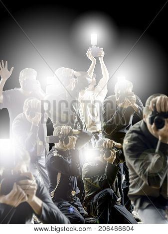 Crowd of paparazzi flashing in front a dark black background.
