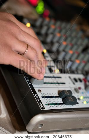 DJ working on a audiomixer at a nightclub. Close-up of hands adjusting quality of music using a knobs of the audio mixer