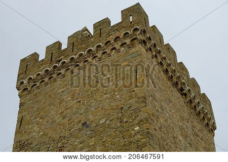 An ancient fortress tower against the background of the autumn sky. Architecture Exterior