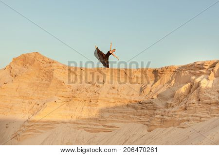 Woman dances high on a sand dune against the sky.