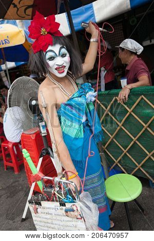 BANGKOK THAILAND - DECEMBER 22 2007 : The Chatuchak Weekend Market is the largest market in Thailand. A man with a clown makeup makes a show.