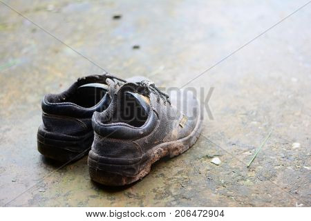 An Old Safety Shoes On Dirty Cement Ground With Light