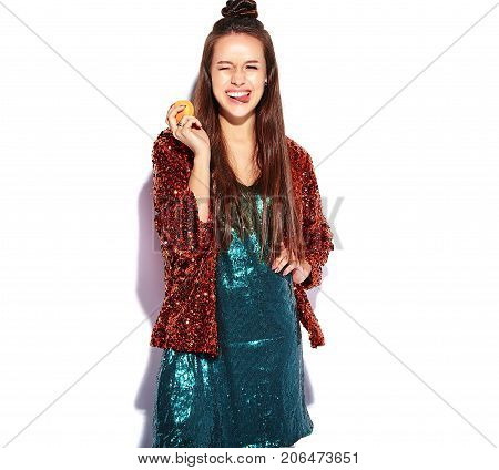 Beautiful caucasian smiling hipster brunette woman model in bright shinny reflecting summer stylish jacket and green dress isolated on white background. Eating french macaroon and showing her tongue
