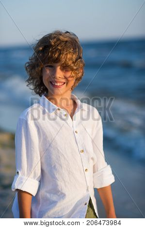 Portrait of boy of 10-11 years against the background of the rough sea. Sea wind ruffled the blond curly hair of the boy. Laddie has blue cheerful eyes suntanned skin a pleasant smile. Boy is dressed in a white shirt.