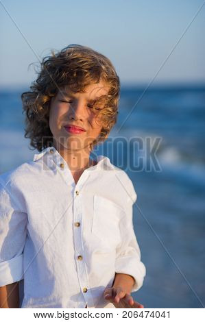 Portrait of boy of 10-11 years against the background of the rough sea. Sea wind ruffled the blond curly hair of the boy. Boy is dressed in a white shirt.